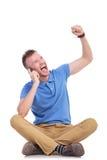 Молодой вскользь человек веселя на его телефоне Стоковые Изображения RF