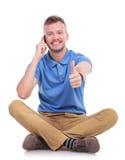 Молодой вскользь человек на телефоне показывает большой палец руки вверх Стоковое фото RF