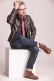 Молодой вскользь человек сидя на белом кубе Стоковая Фотография