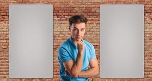 Молодой вскользь человек думая около 2 пустых афиш Стоковая Фотография RF