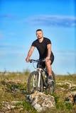 Молодой горный велосипед катания велосипедиста спортсмена на скалистом следе в сельской местности Стоковое Изображение