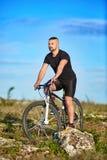 Молодой горный велосипед катания велосипедиста спортсмена на скалистом следе в сельской местности Стоковое фото RF