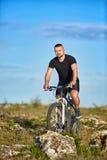 Молодой горный велосипед катания велосипедиста спортсмена на скалистом следе в сельской местности Стоковое Изображение RF