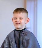 Молодой гримасничая мальчик получая отрезок волос Стоковая Фотография RF