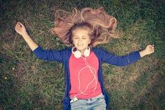 Молодой девочка-подросток ослабляя и лежа на зеленой траве Стоковая Фотография