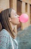 Молодой девочка-подросток дуя розовая жевательная резинка Стоковое Изображение