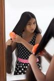 Молодой девочка-подросток чистя ее волосы щеткой Стоковое Фото