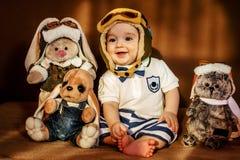 Молодой летчик сидя с его мягкими игрушками стоковое фото