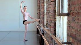 Молодой женский артист балета работая в классе балета акции видеоматериалы