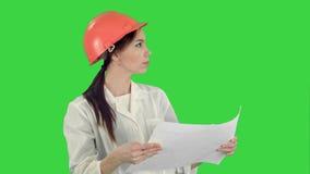 Молодой женский архитектор держа светокопии и проверяя конструкцию на зеленом экране, ключ Chroma сток-видео