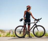 Молодой женский велосипедист смотря прочь стоковые изображения rf