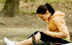 Молодой женский велосипедист с ногой повреждения стоковые фотографии rf