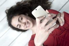Молодой женский лежать на поле принимая selfie Стоковые Фото