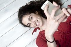 Молодой женский лежать на поле принимая selfie Стоковые Фотографии RF