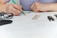 Молодой женский дизайнер работая с архитектурноакустическим планом Стоковые Фото