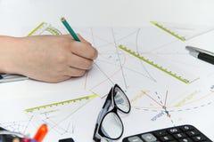 Молодой женский дизайнер работая с архитектурноакустическим планом Стоковые Изображения