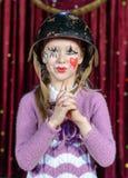 Молодой женский клоун делая оружие из сжиманных рук Стоковые Изображения