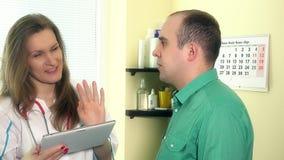 Молодой женский доктор объясняя курс обработки для потревоженного мужского пациента акции видеоматериалы