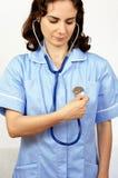 Молодой женский доктор проверяя ее собственное сердцебиение используя изолированный стетоскоп, Стоковые Изображения RF
