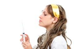Молодой женский доктор смотря иглу шприца Стоковые Фото