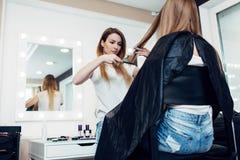 Молодой женский парикмахер держа стренгу расчесывая волосы девушки s длиной справедливые в салоне красоты Стоковая Фотография RF