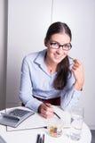 Молодой женский профессионал усмехается пока ел помадки стоковое фото rf