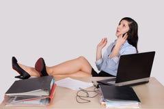 Молодой женский работник офиса с ногами на столе Стоковое фото RF