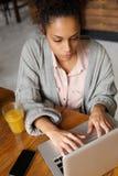 Молодой женский работник печатая на компьтер-книжке Стоковое Фото
