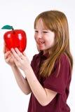 Женский ребенок школьного возраста держа ясное пластичное яблоко Стоковое фото RF