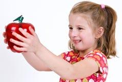 Женский ребенок школьного возраста держа ясное пластичное яблоко Стоковые Изображения RF