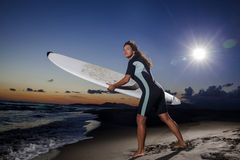 Молодой женский серфер на пляже в заходе солнца Стоковые Фото