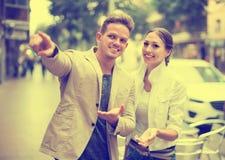 Молодой женский турист просит направления от человека стоковое фото rf