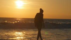 Молодой женский турист с рюкзаком идя вдоль пляжа моря на заходе солнца Красивая молодая женщина путешественника идя на океан Стоковое Фото