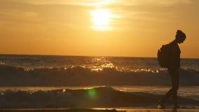 Молодой женский турист с рюкзаком идя вдоль пляжа моря на заходе солнца Красивая молодая женщина путешественника идя на океан Стоковые Изображения