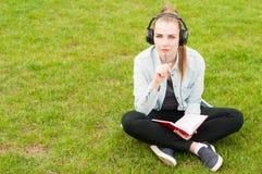 Молодой женский думать и запись пока слушая музыка outdoors Стоковое Фото