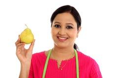 Молодой женский шеф-повар держа яблоко груш против белизны Стоковые Изображения RF