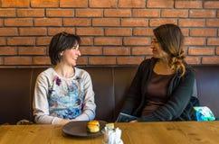 2 молодой женщины брюнет сидя в кафе имея переговор Стоковые Фотографии RF