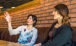 2 молодой женщины брюнет сидя в кафе имея переговор Стоковое Фото