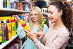 2 молодой женщины выбирая мусс волос styiling Стоковая Фотография RF