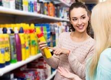 2 молодой женщины выбирая мусс волос styiling Стоковые Изображения