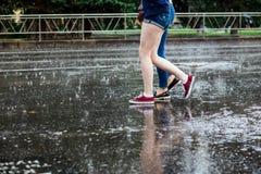 2 молодой женщины в ботинках пересекая ноги улицы во время проливного дождя Стоковые Изображения