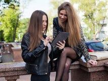 2 молодой женщины в городе смотрят экран Стоковые Фотографии RF