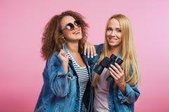 2 молодой женщины в джинсовой ткани с солнечными очками и биноклями Стоковые Фотографии RF