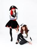 2 молодой женщины в костюмах пирата на белой предпосылке Стоковые Фото