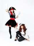 2 молодой женщины в костюмах пирата на белой предпосылке Стоковая Фотография RF