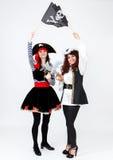 2 молодой женщины в костюмах пирата на белой предпосылке Стоковое Изображение RF