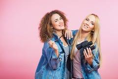2 молодой женщины в куртках джинсов джинсовой ткани с солнечными очками и биноклями Стоковые Фото
