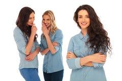 2 молодой женщины говоря за задней частью их руководителя Стоковое Фото