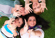 4 молодой женщины лежа на зеленой траве с руками вверх Стоковое Изображение
