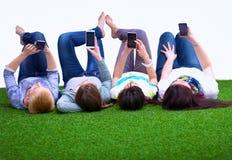 4 молодой женщины лежа на зеленой траве Стоковая Фотография RF